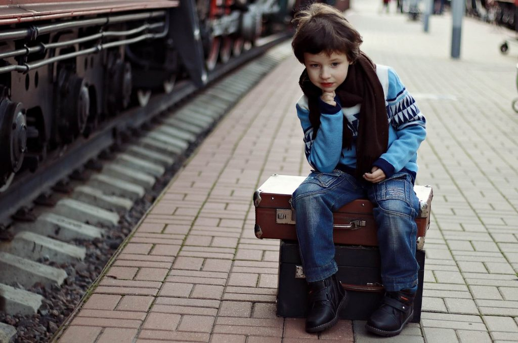 Sad boy sitting on a suitcase at a railway station