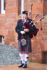 Piper at Fonab Castle welcoming guests on a Hogmanay break at a Scottish castlel