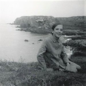 Black and white picture of a little girl sitting on top of a cliff overlooking the sea