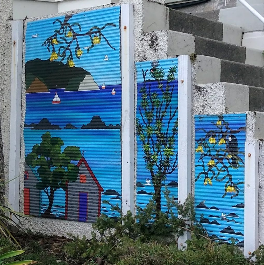 Mural of a seaside scene on the side of a stairway - an example of street art in eastern Wellington
