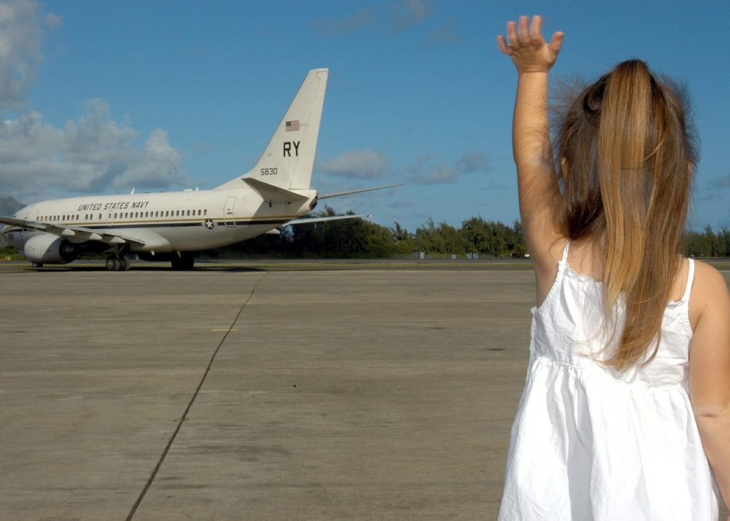 Child waving off a US military aircraft