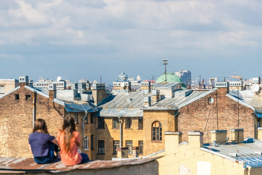 Two friends sitting on a roof overlooking a city