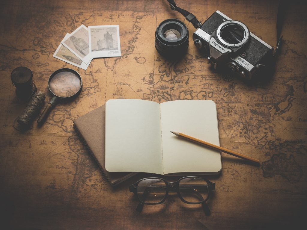Picture of map, notebook, pencil, camera, spyglass, and postcards - essential for travellers along with travel insurance