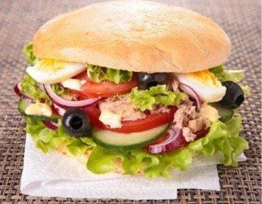 Pan bagnat - Nicoise sandwich with tuna, olives, tomatoes, radish, egg, lettuce and lemon juice