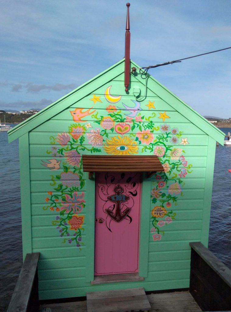 Green boat shed in Evans Bay Wellington with colourful flowers painted on it