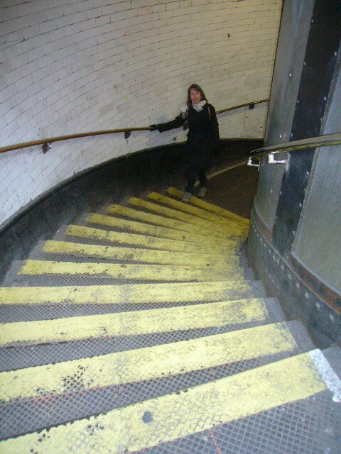 Woman coming up the steps of the Greenwich foot tunnel in London