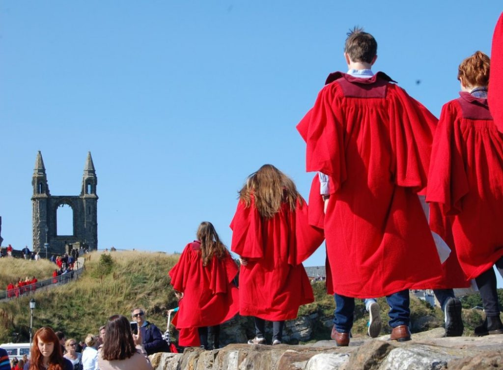 St Andrews students in scarlet gowns walking along the town's pier
