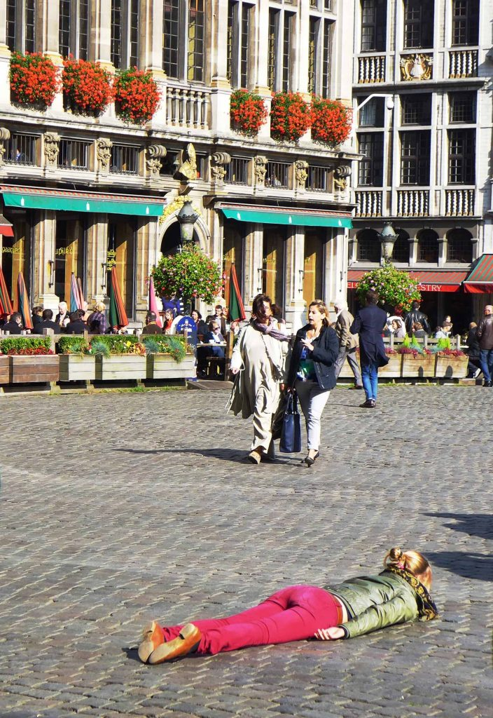 Woman planking in the Grand Place, Brussels. Self-care might be needed when trying to cope with hotel technology!