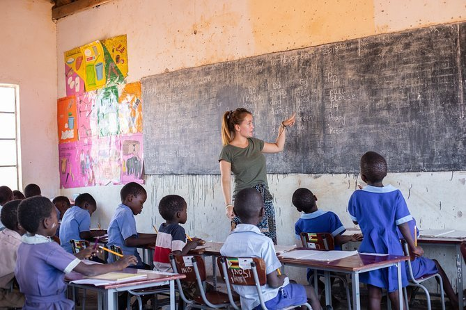 Teacher pointing to blackboard in front of children in classroom in Zimbabwe