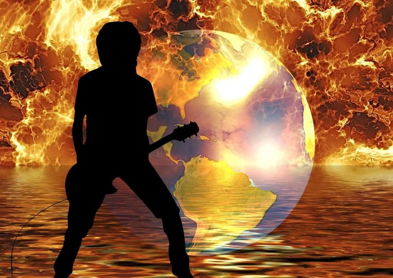 silhouette of a rock star in front of a fiery globe