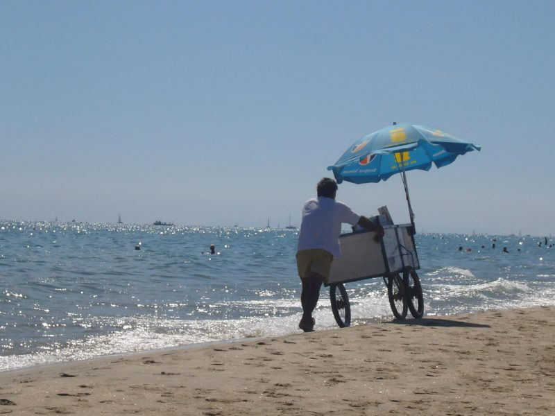 Refreshment trolley being pushed along the beach at Marseillan Plage France
